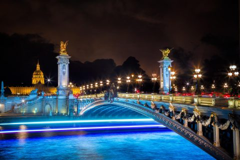 pont bridge alexandre III in paris at night with boat lights on the Seine River