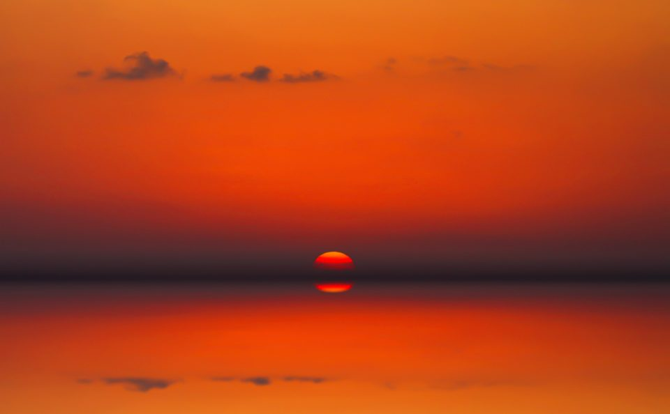 landscape with red sun reflected in the ocean