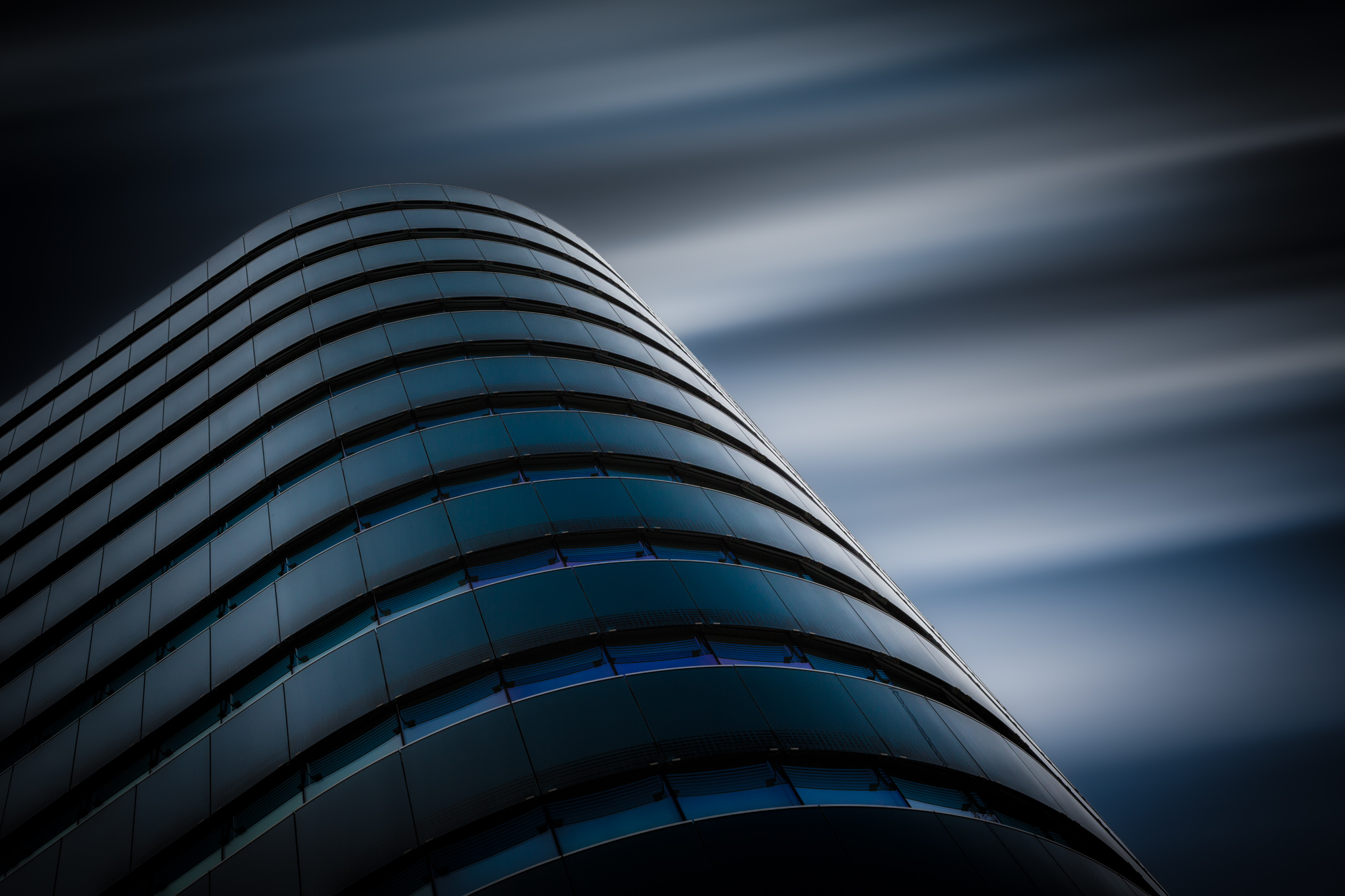 long exposure photograph of curved blue glass modern architecture