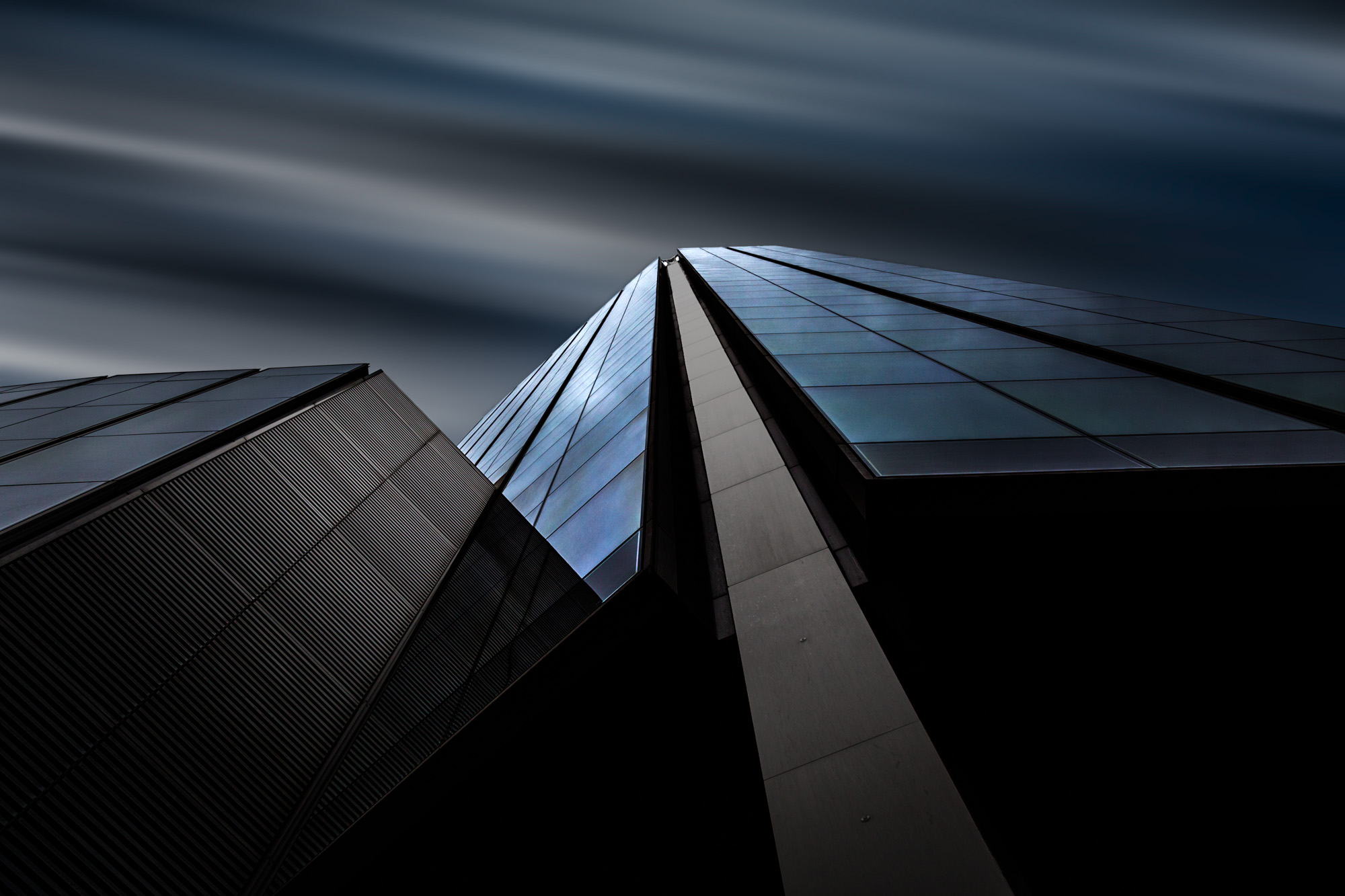 long exposure photograph of blue glass modern skyscraper architecture