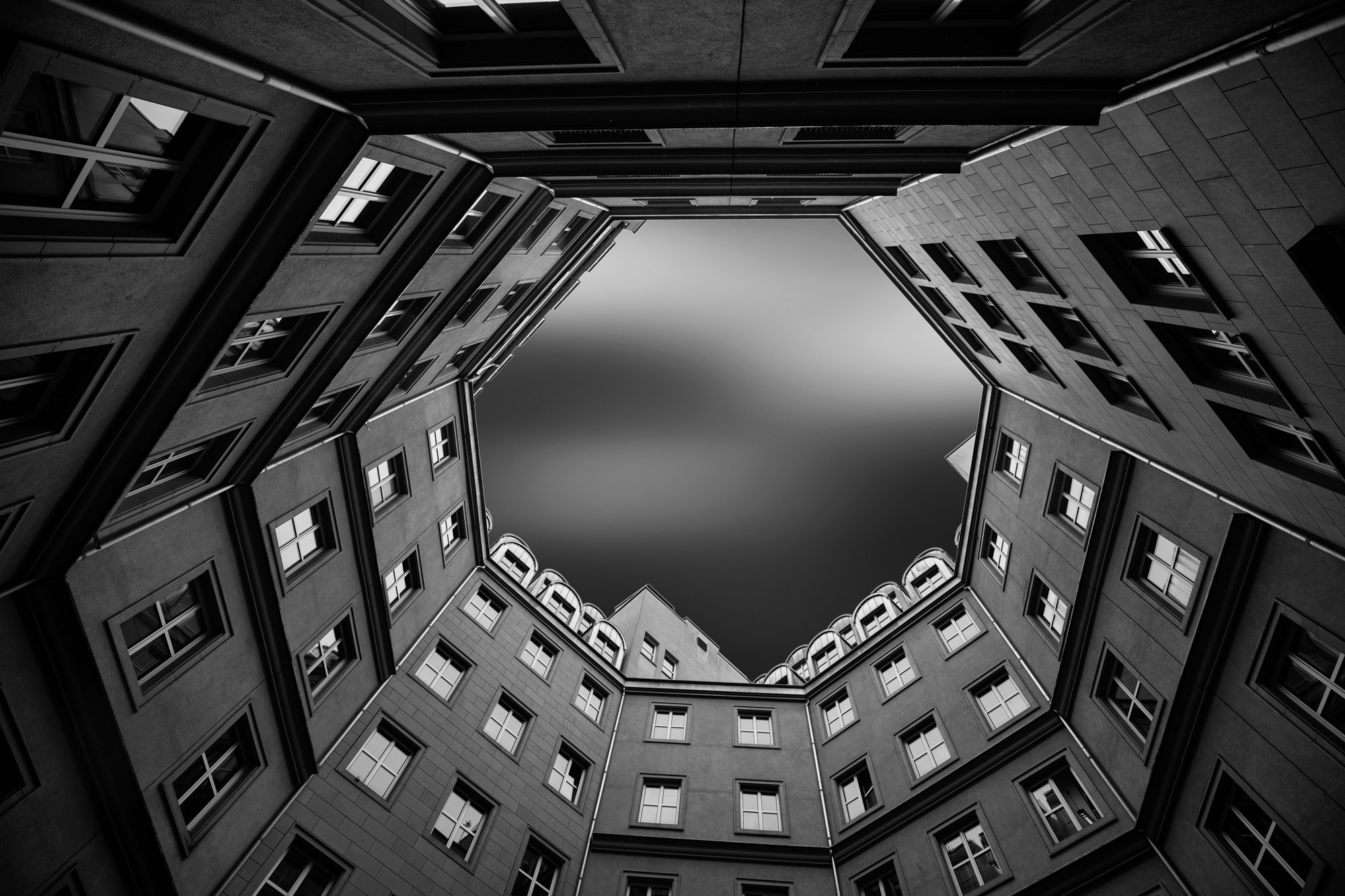 long exposure architecture photograph looking up through courtyard to sky in modern building