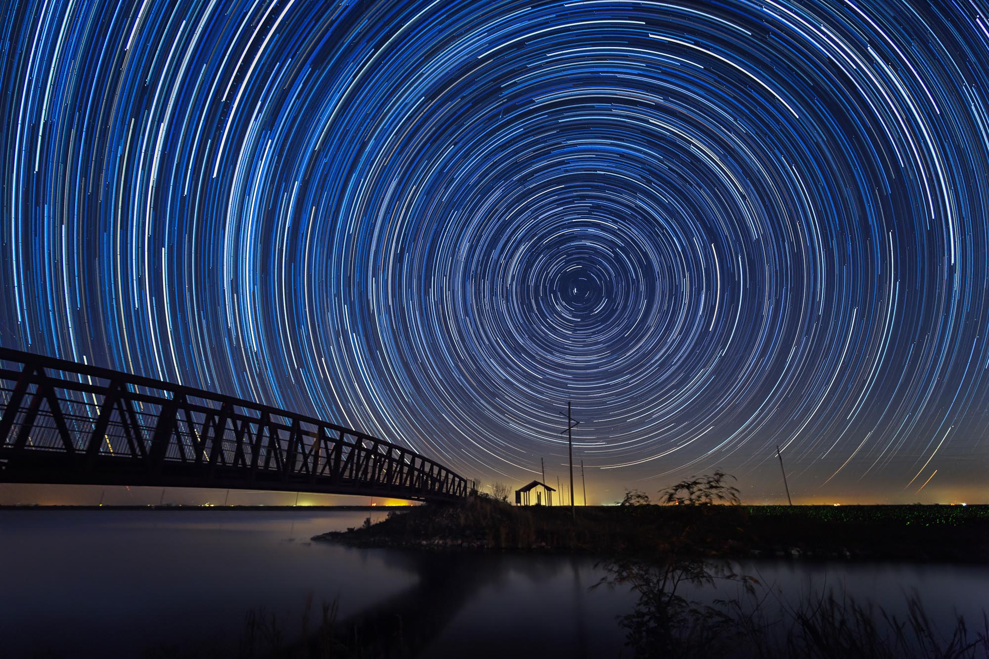 long exposure astrophotography of star trails in the Florida Everglades by a bridge and fishing hut