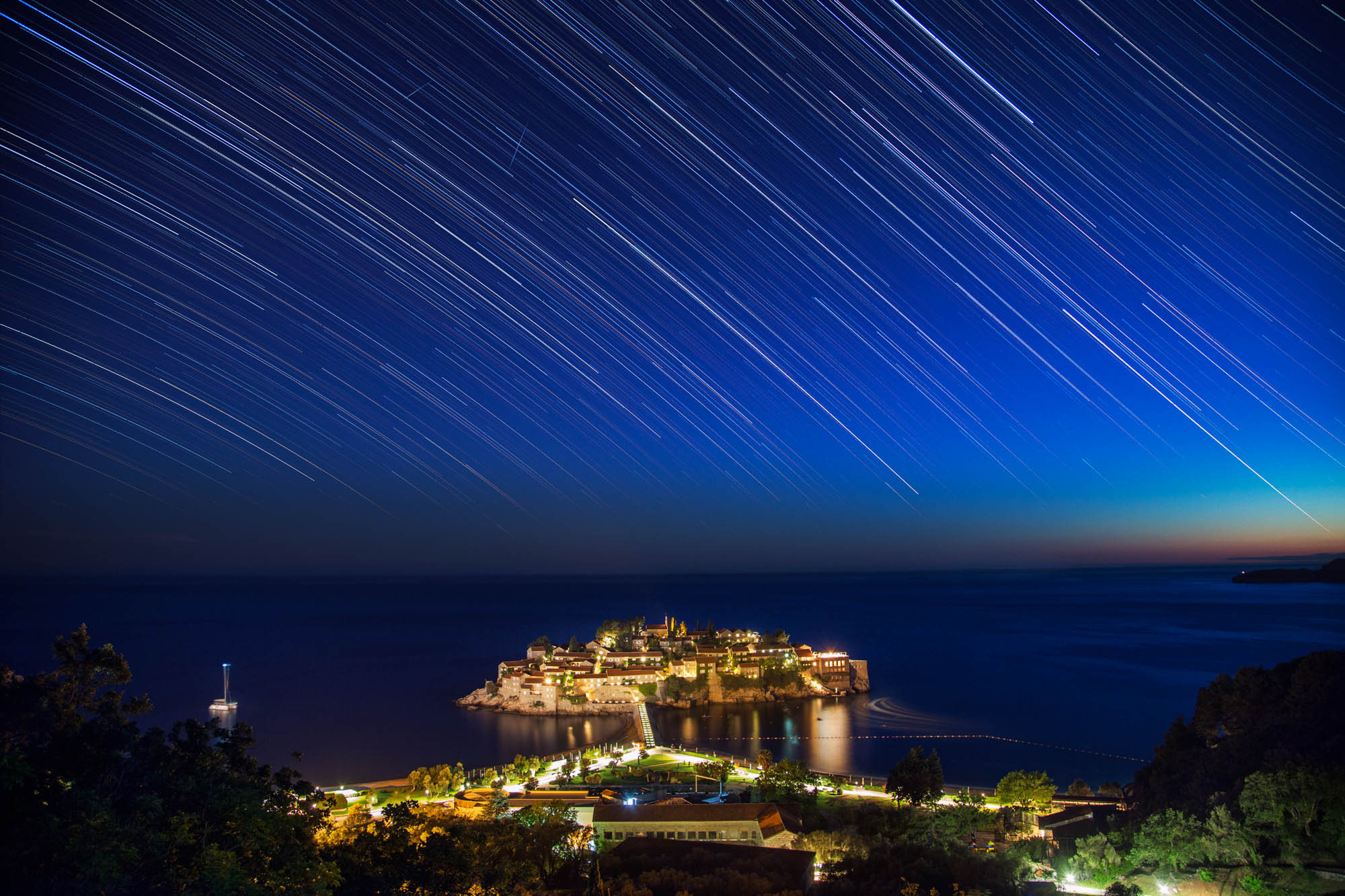 long exposure astrophotography of star trails in Sveti Stefan in Montenegro