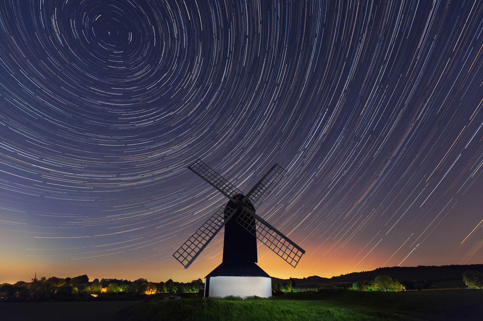 long exposure astrophotography of star trails around an old windmill in England UK