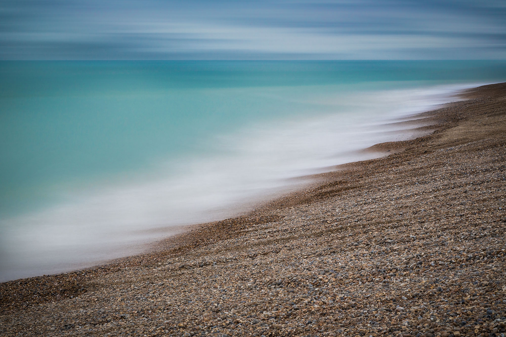 minimal abstract long exposure photograph blurring the rushing tides on a stone pebble beach in Sussex UK