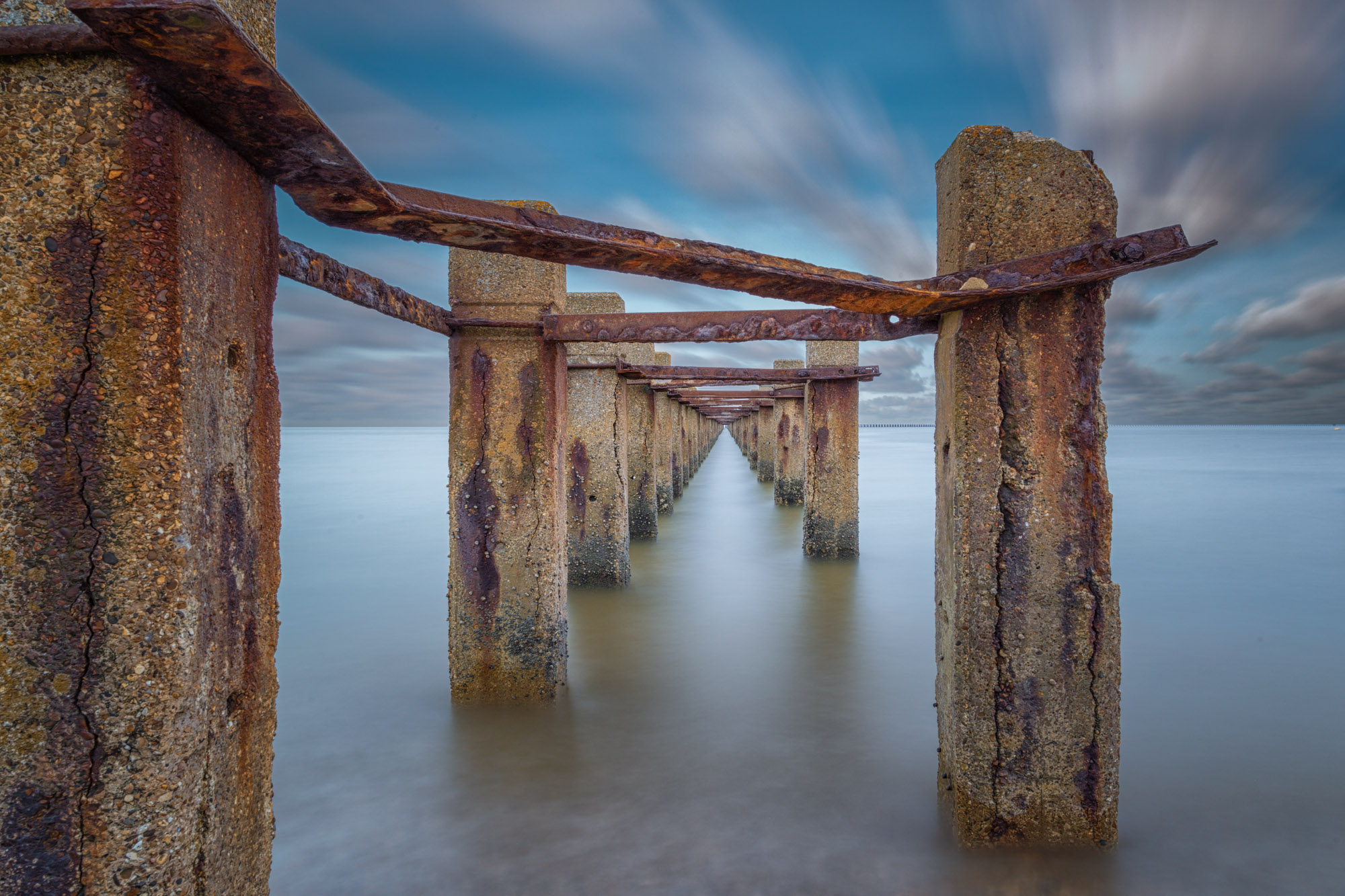 minimal long exposure photograph of an old derelict jetty structure in the ocean in the UK