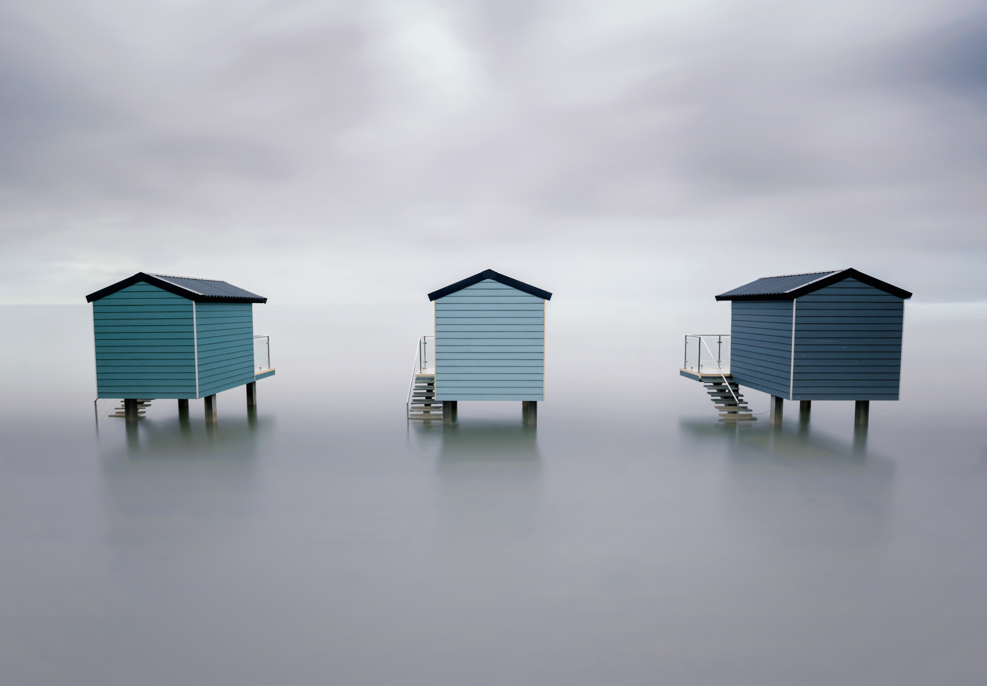 minimal long exposure photograph of three fishing huts in the ocean in the UK