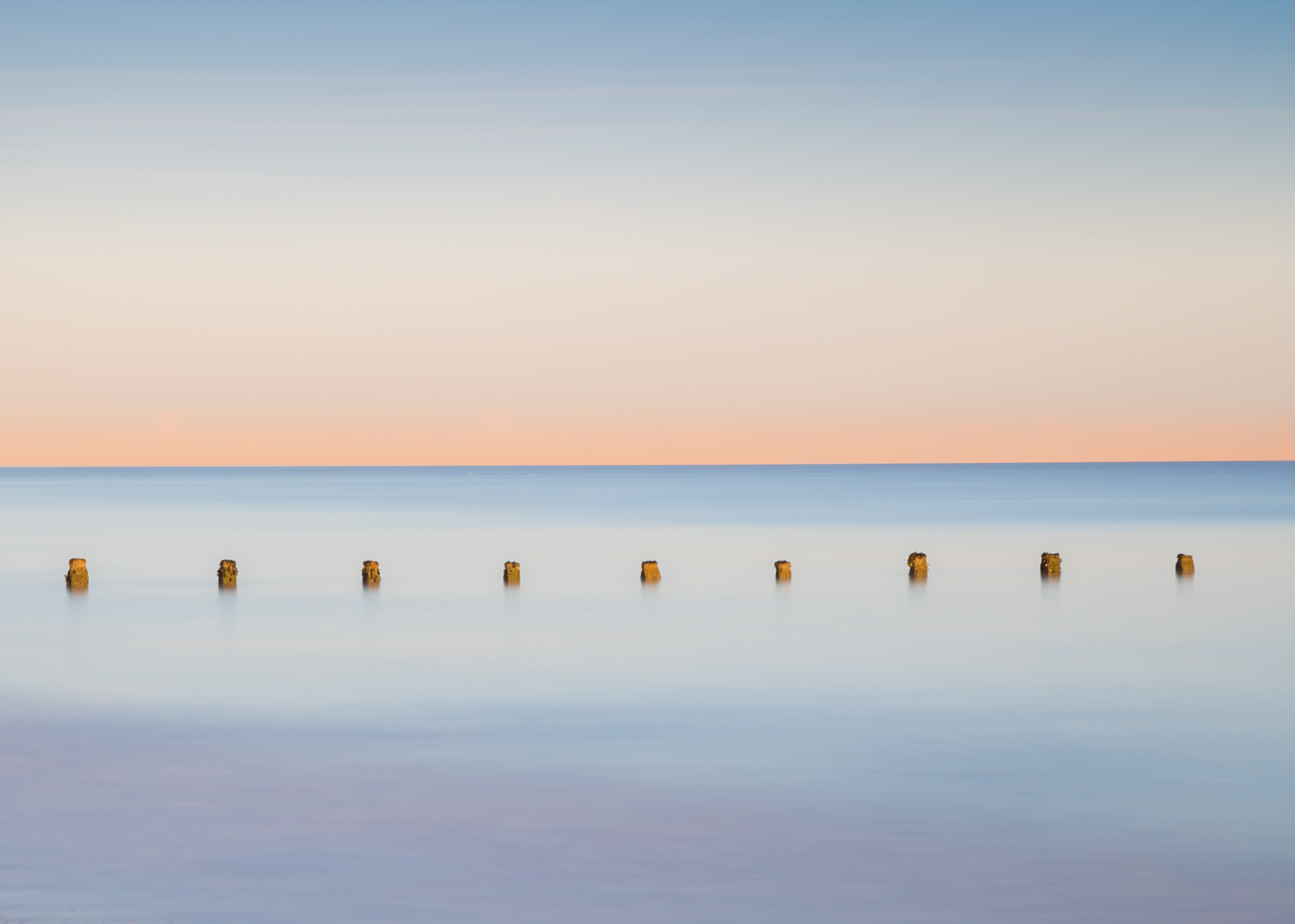 antonyz long exposure landscape minimal photograph of posts in the sea