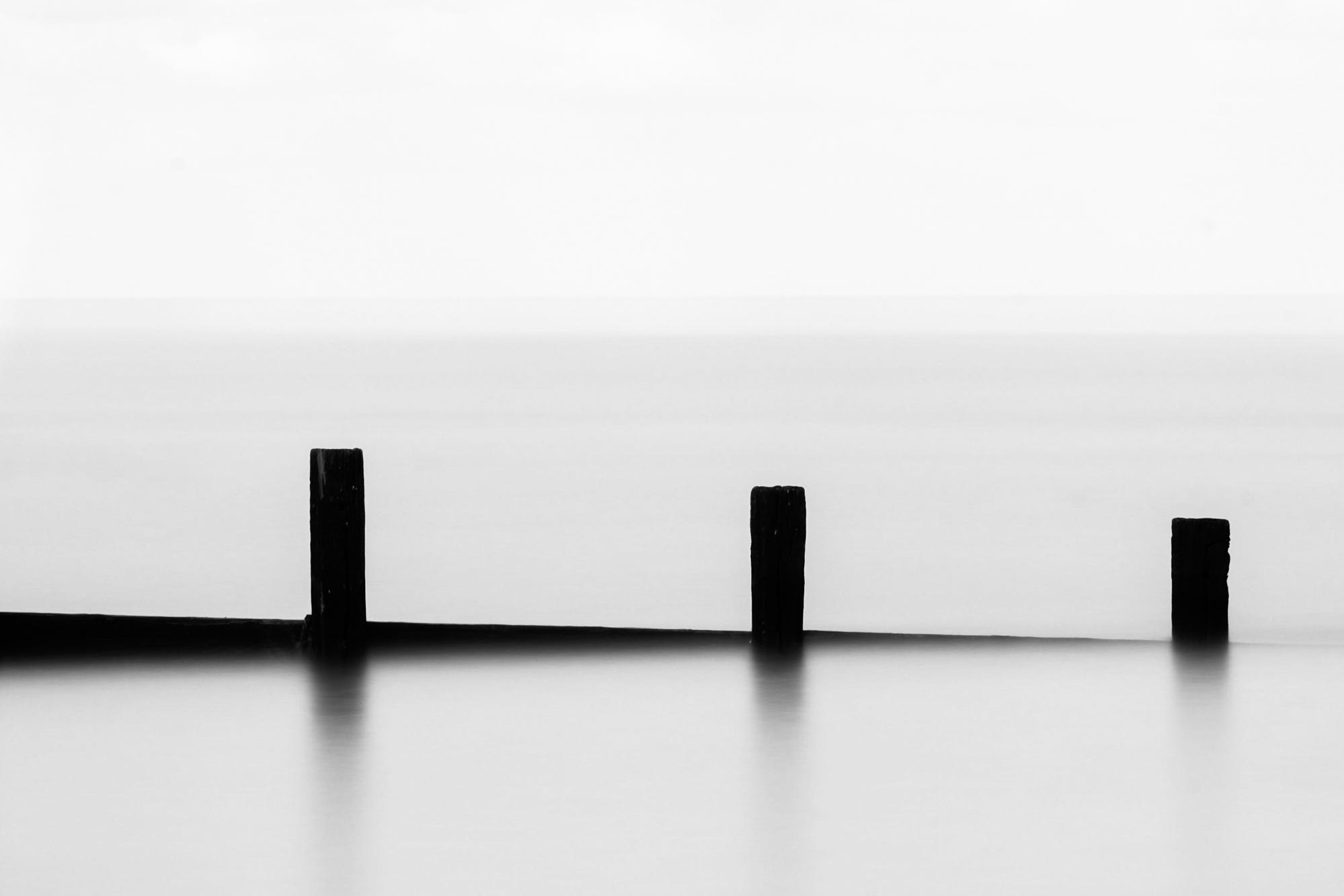 antonyz long exposure landscape minimal photograph of wooden posts in the sea