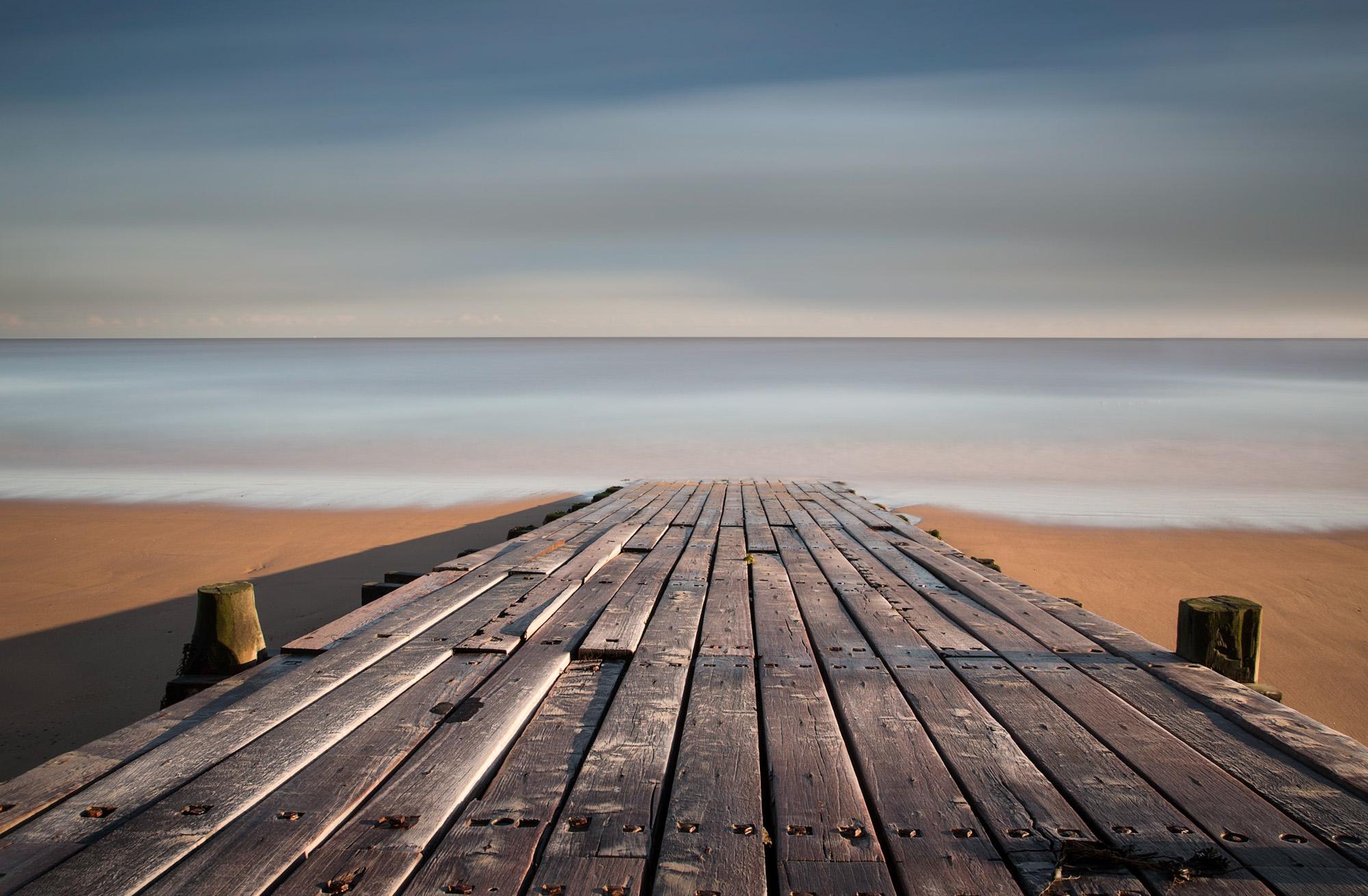 antonyz long exposure landscape photograph of a wooden boardwalk facing the sea