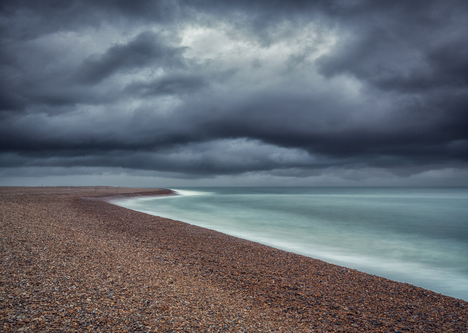 antonyz long exposure landscape minimal photograph of stormy skies over a shingle beach in the UK