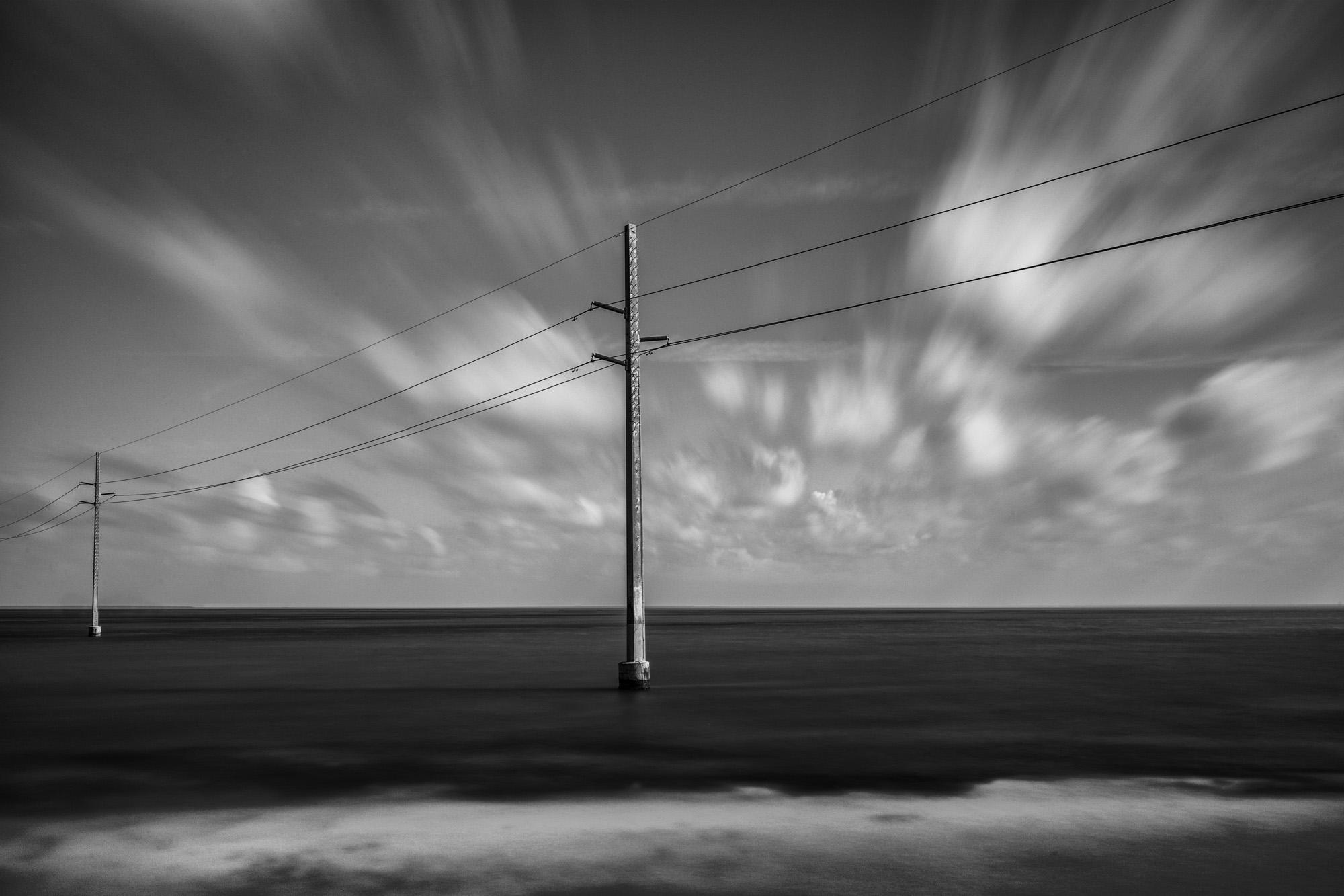 antonyz long exposure landscape photograph of telegraph posts in the ocean