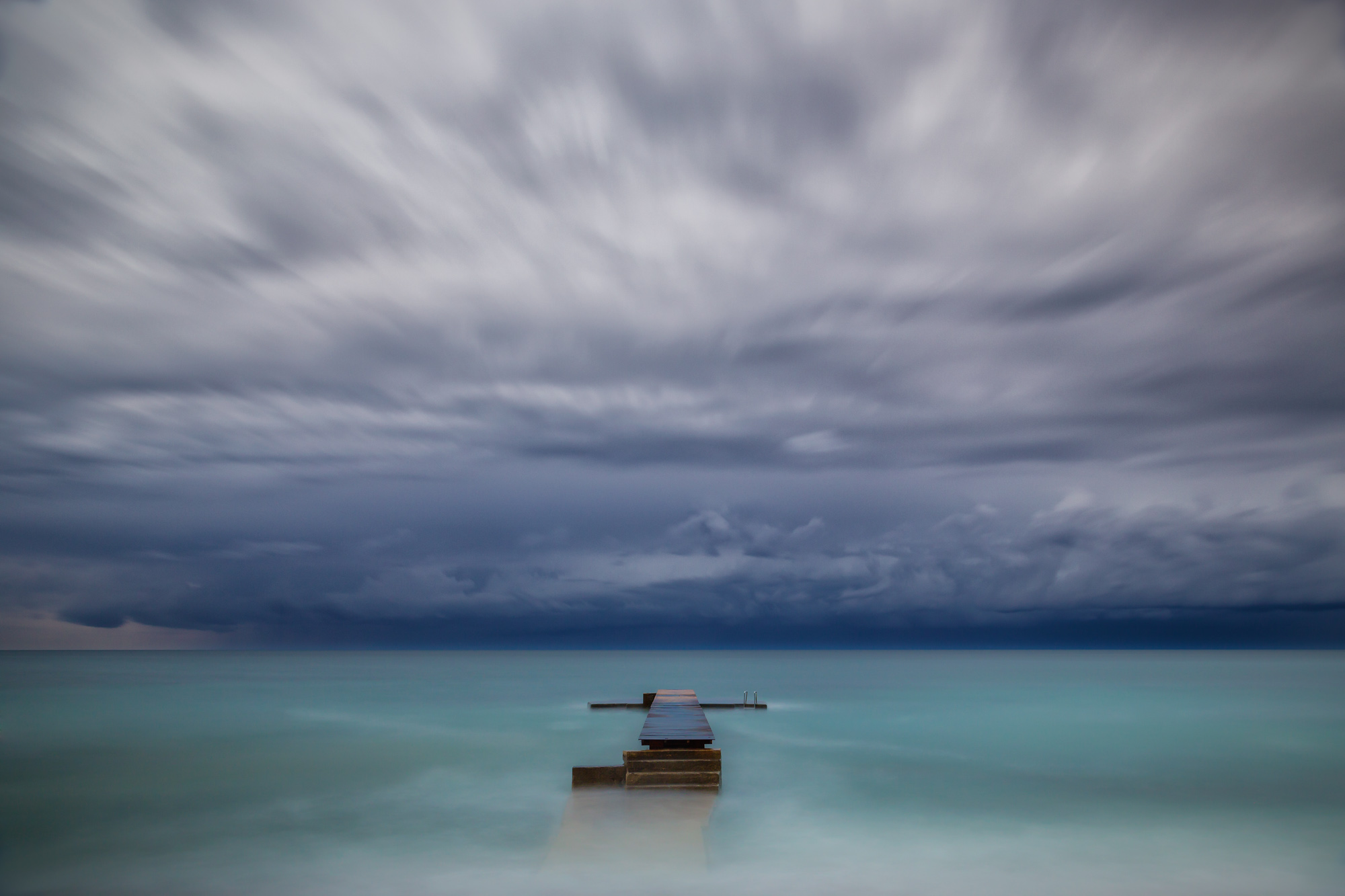 minimal long exposure photograph of a wooden jetty in the ocean with a storm approaching