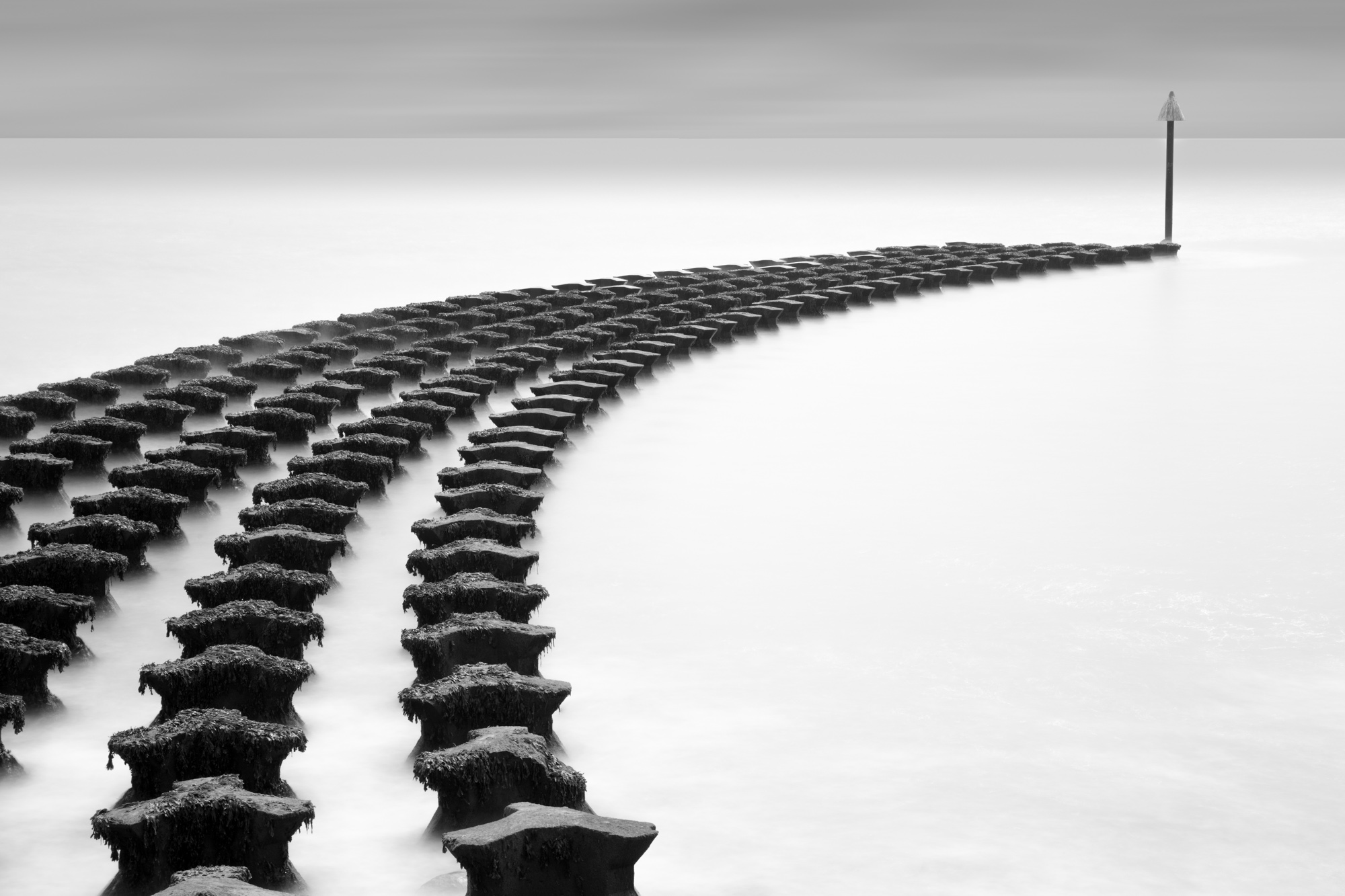 minimal long exposure photograph of an arch of groins in the ocean in the UK