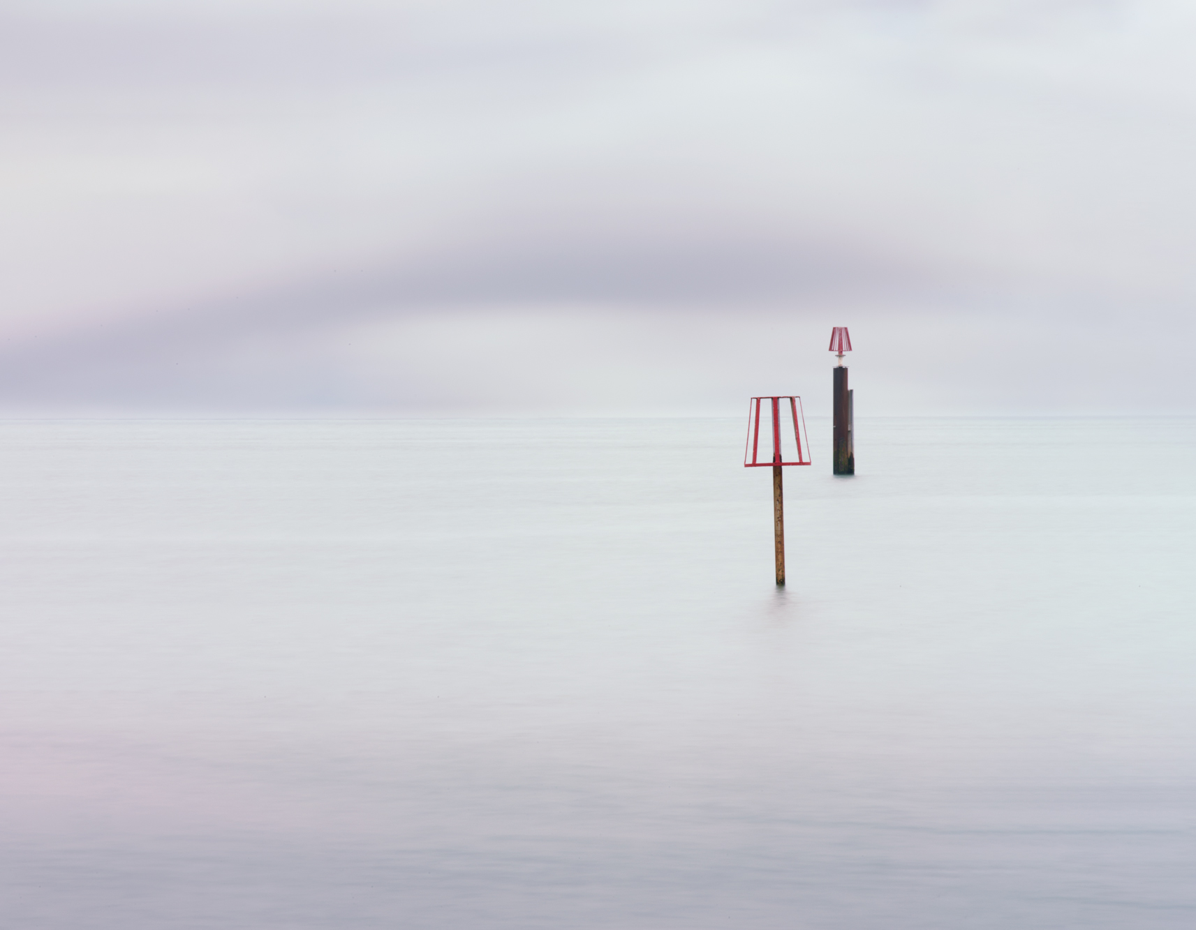 minimal long exposure photograph of two posts in the ocean at sunset in the UK