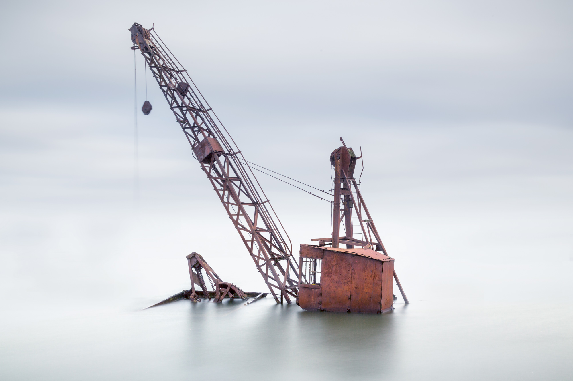 antonyz long exposure landscape photograph of a derelict crane in a flooded quarry in the UK