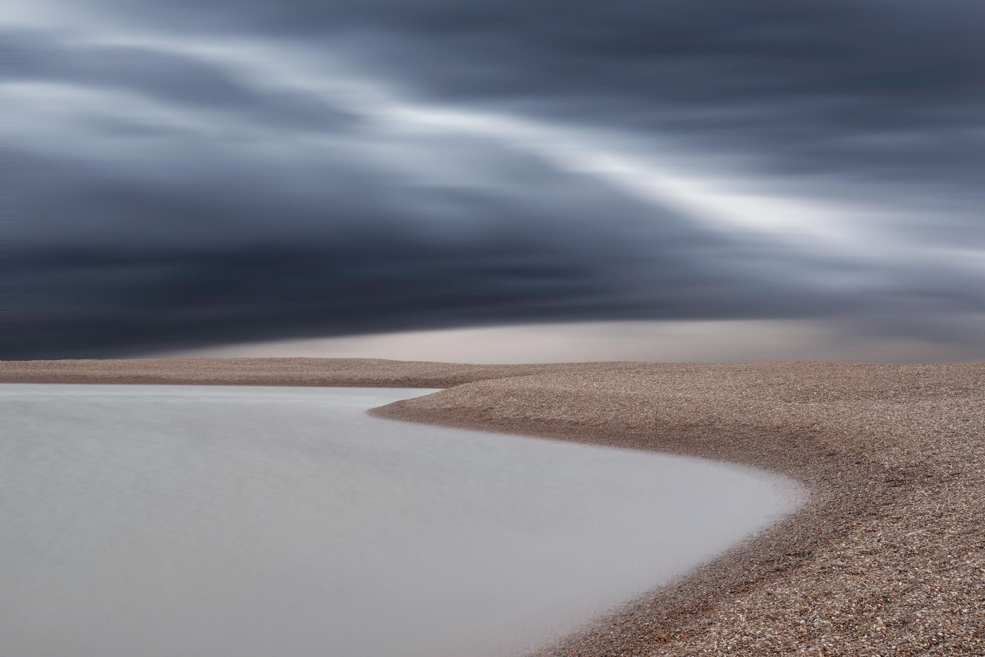 minimal long exposure photograph of a storm over a shingle beach