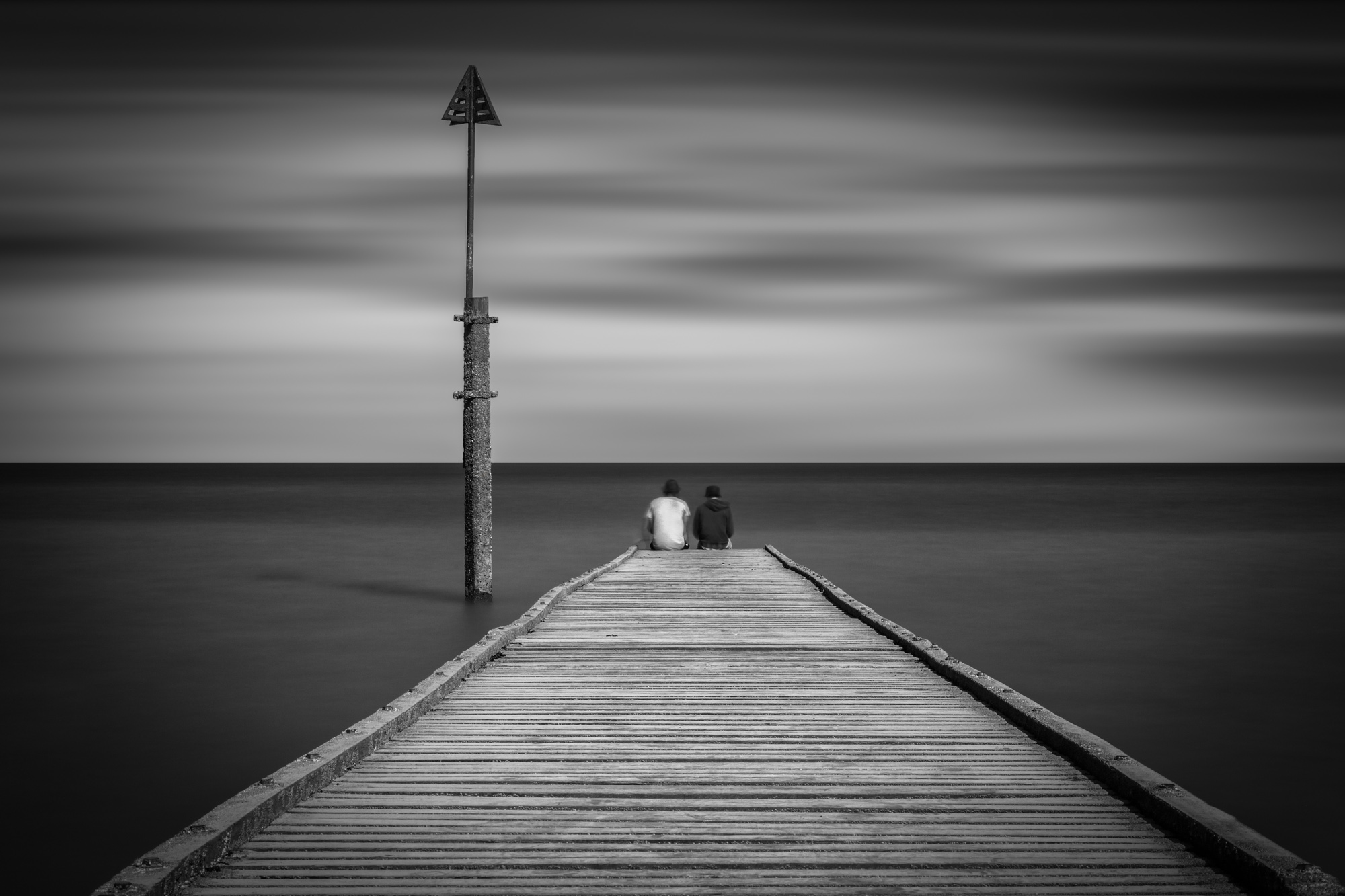 antonyz long exposure landscape photograph of two friends sitting at the end of a jetty