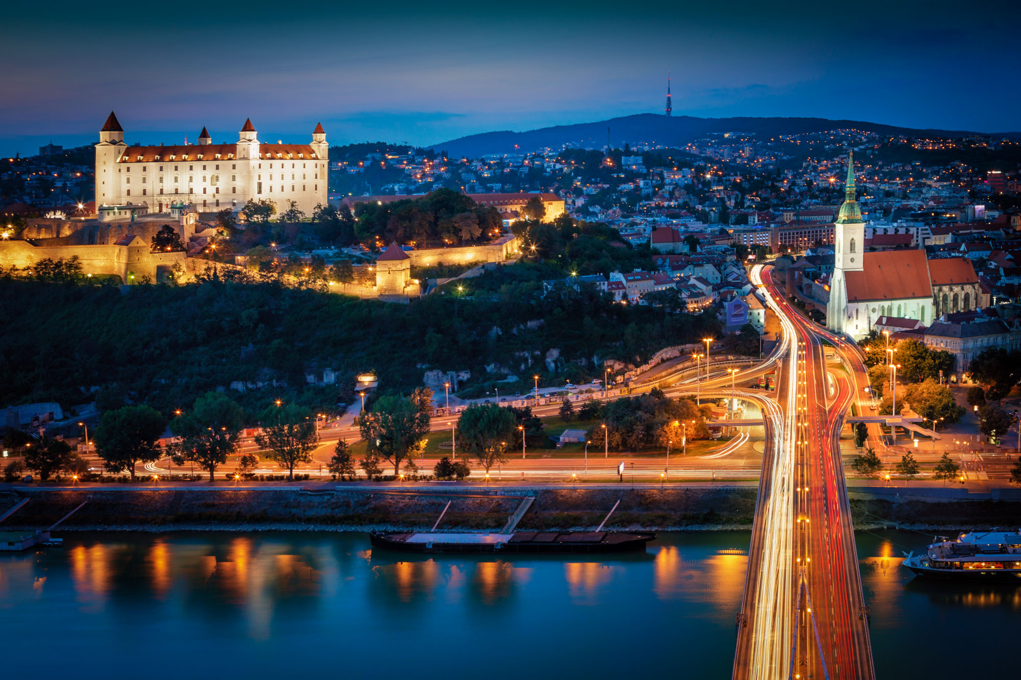 long exposure night photography of Bratislava Castle and Church illuminated at night by the River Danube and with traffic light trails viewed from above