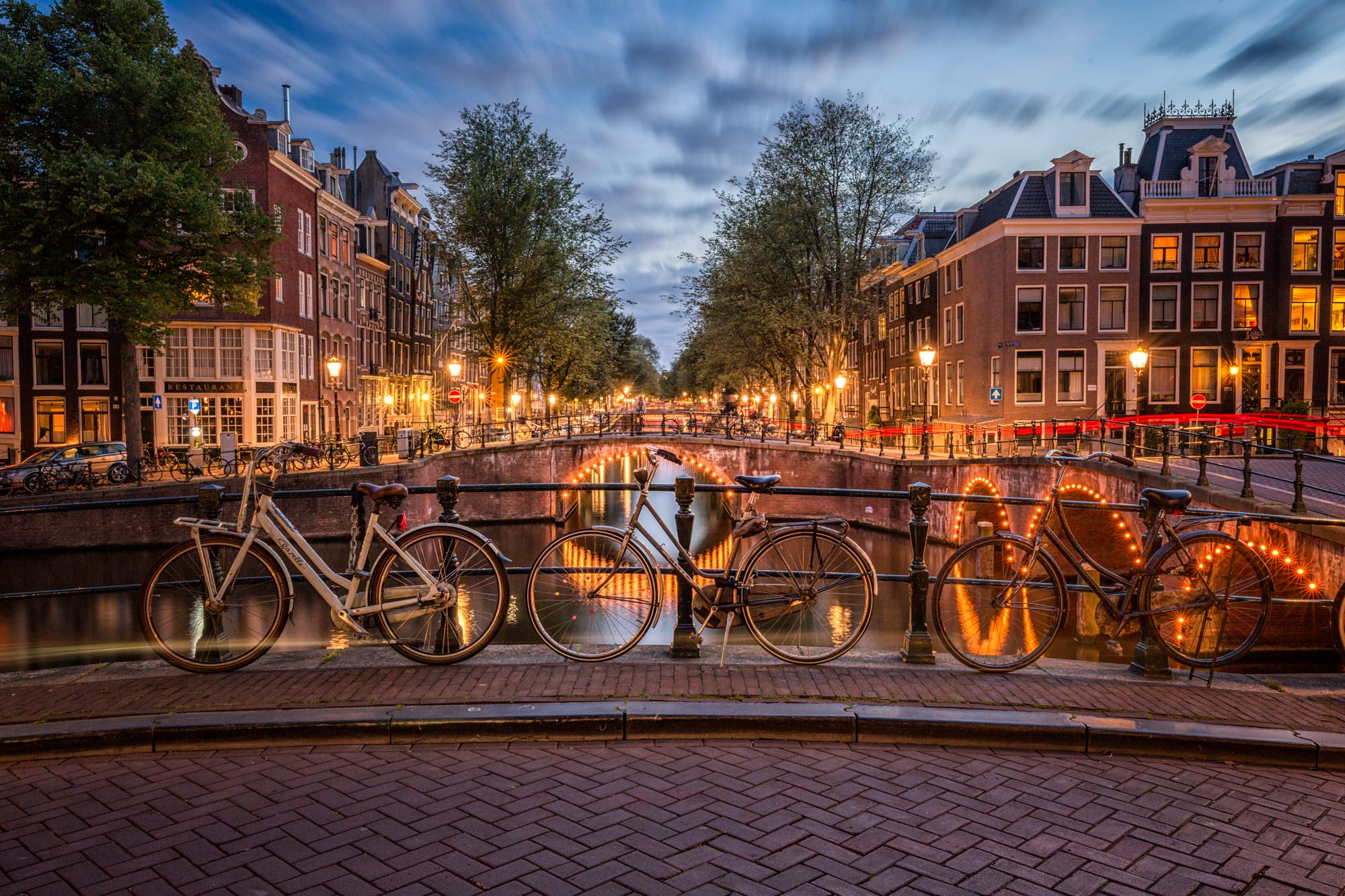 long exposure photography of the bicycles beside a canal in Amsterdam at night in The Netherlands