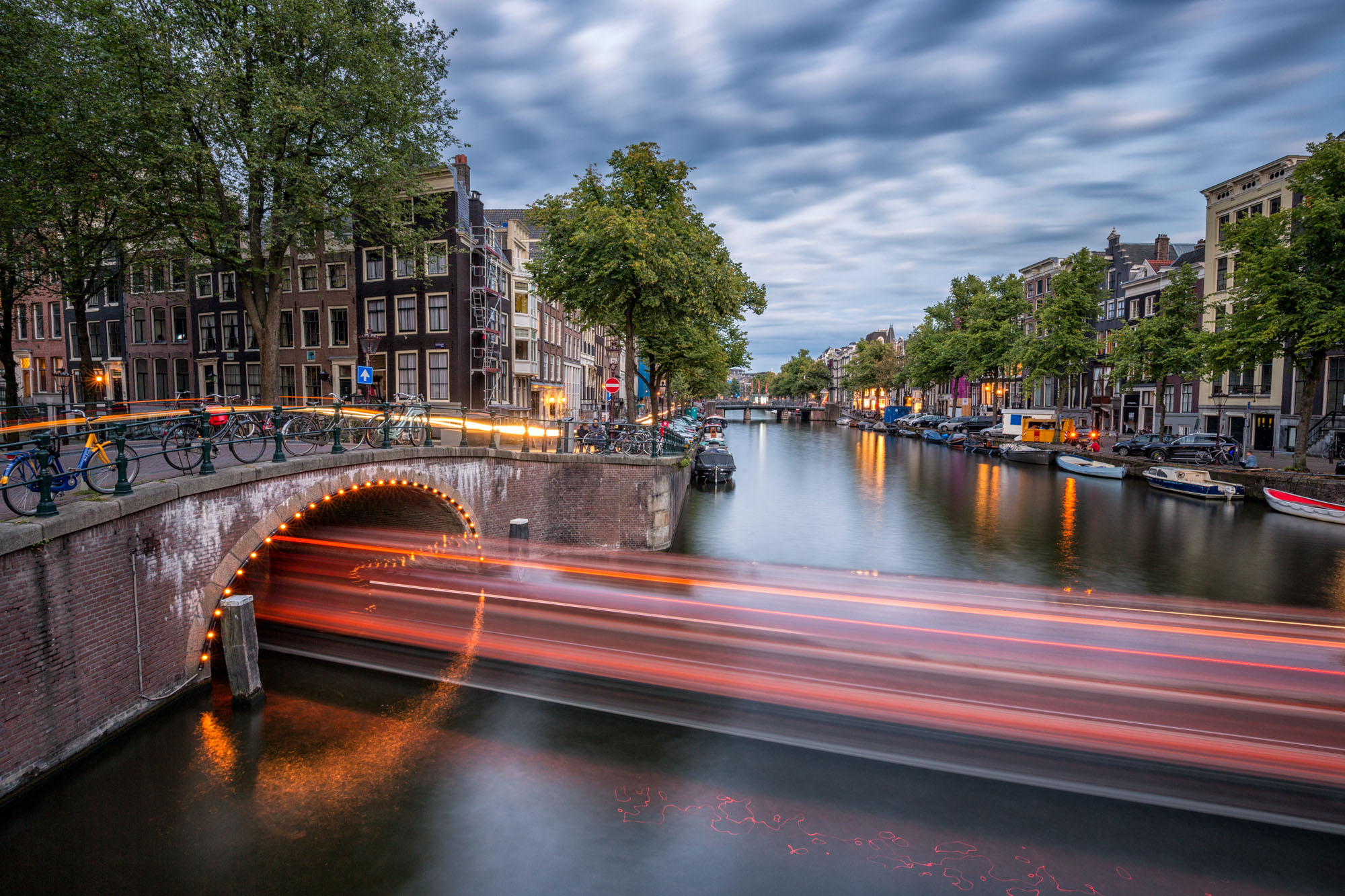 long exposure photography of the light trials of a canal boat in Amsterdam at night in The Netherlands