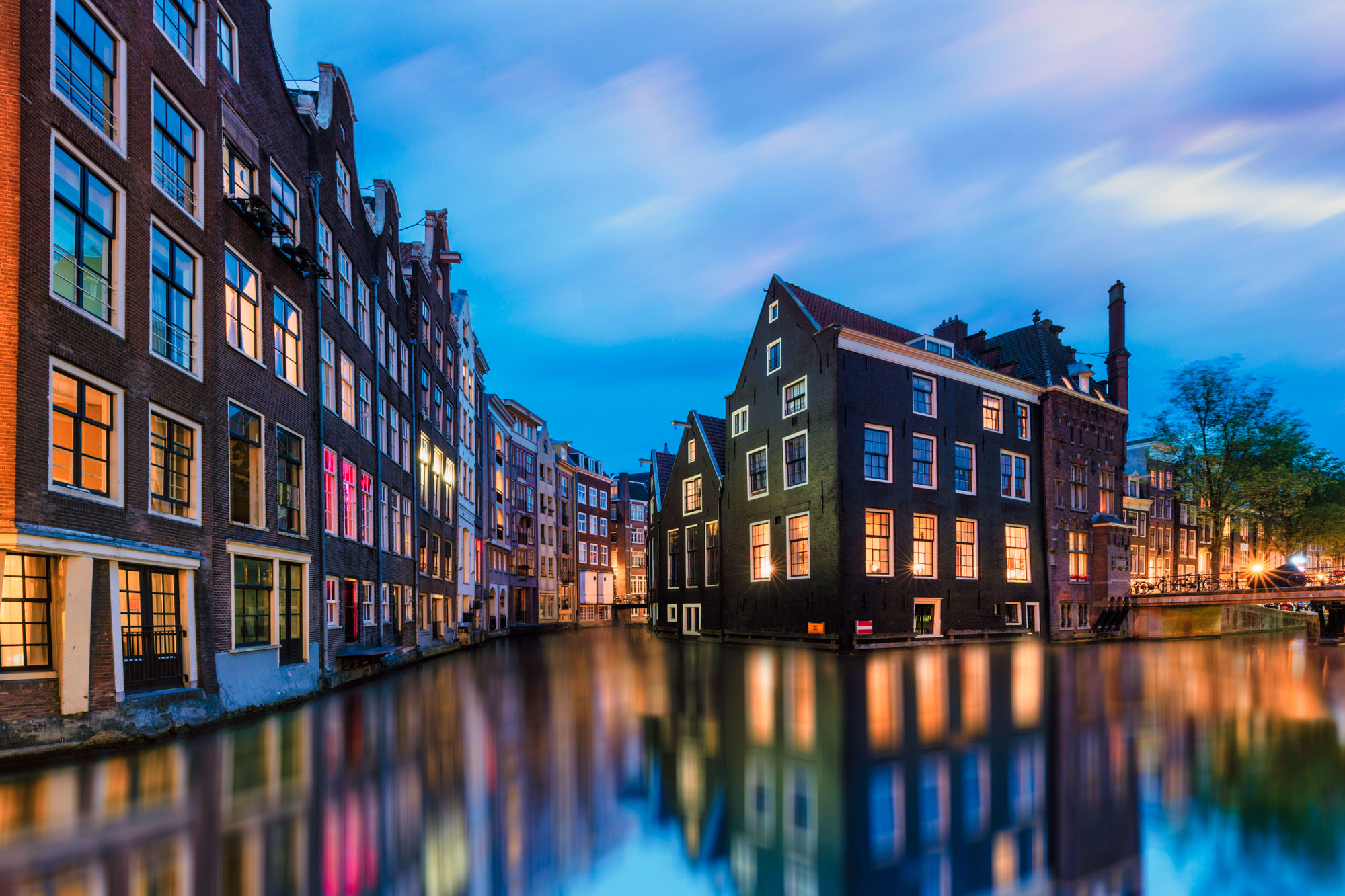 long exposure photography of the architecture in Amsterdam at night beside a canal in The Netherlands
