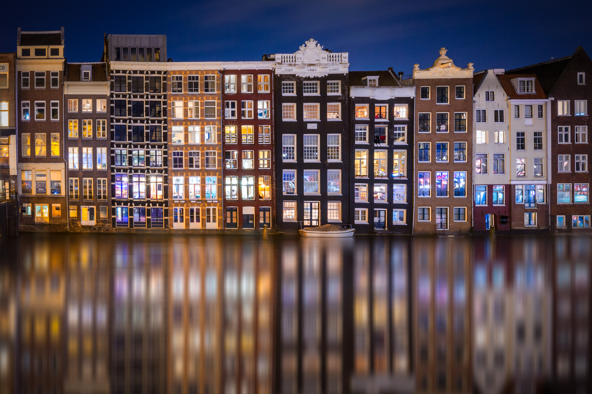long exposure photography of the architecture reflected in a canal in Amsterdam at night in The Netherlands