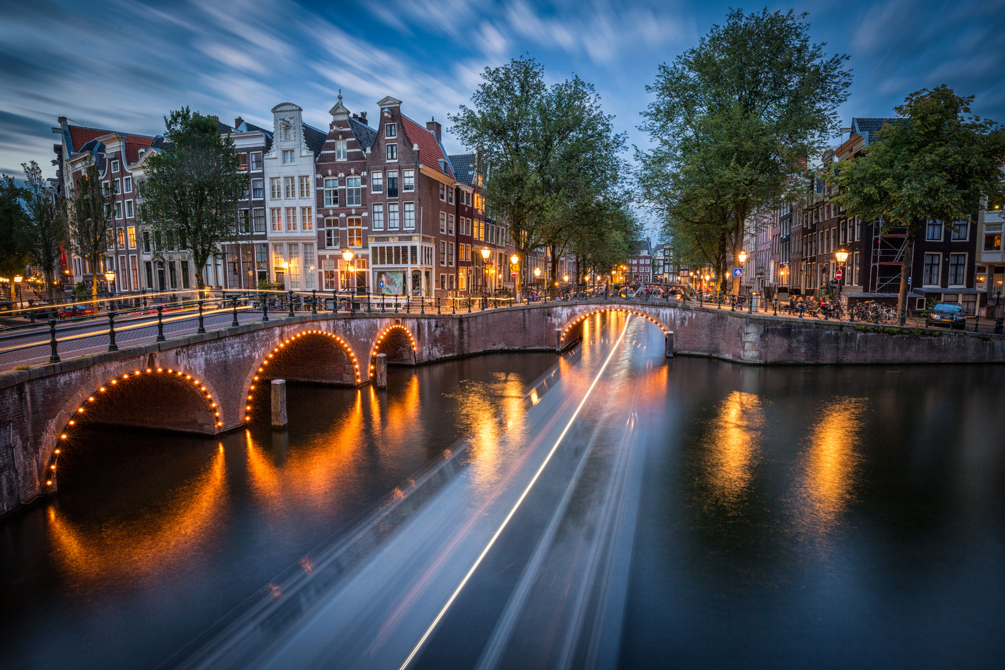 long exposure photography of the light trials of a canal boat beside architecture in Amsterdam at night in The Netherlands