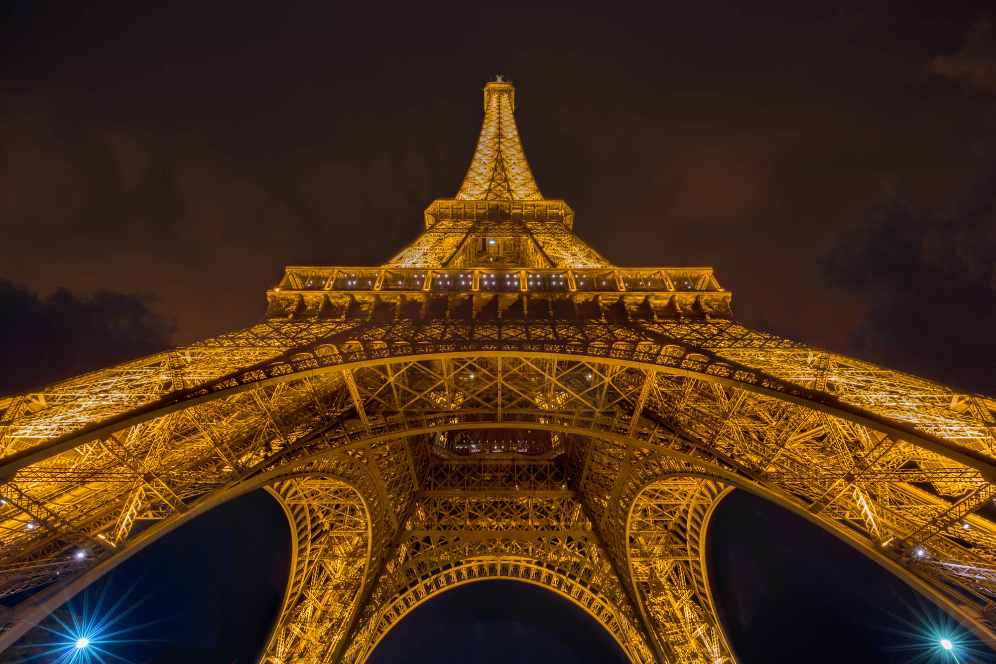 long exposure photography of the Eiffel Tower lit up and viewed from below in Paris France