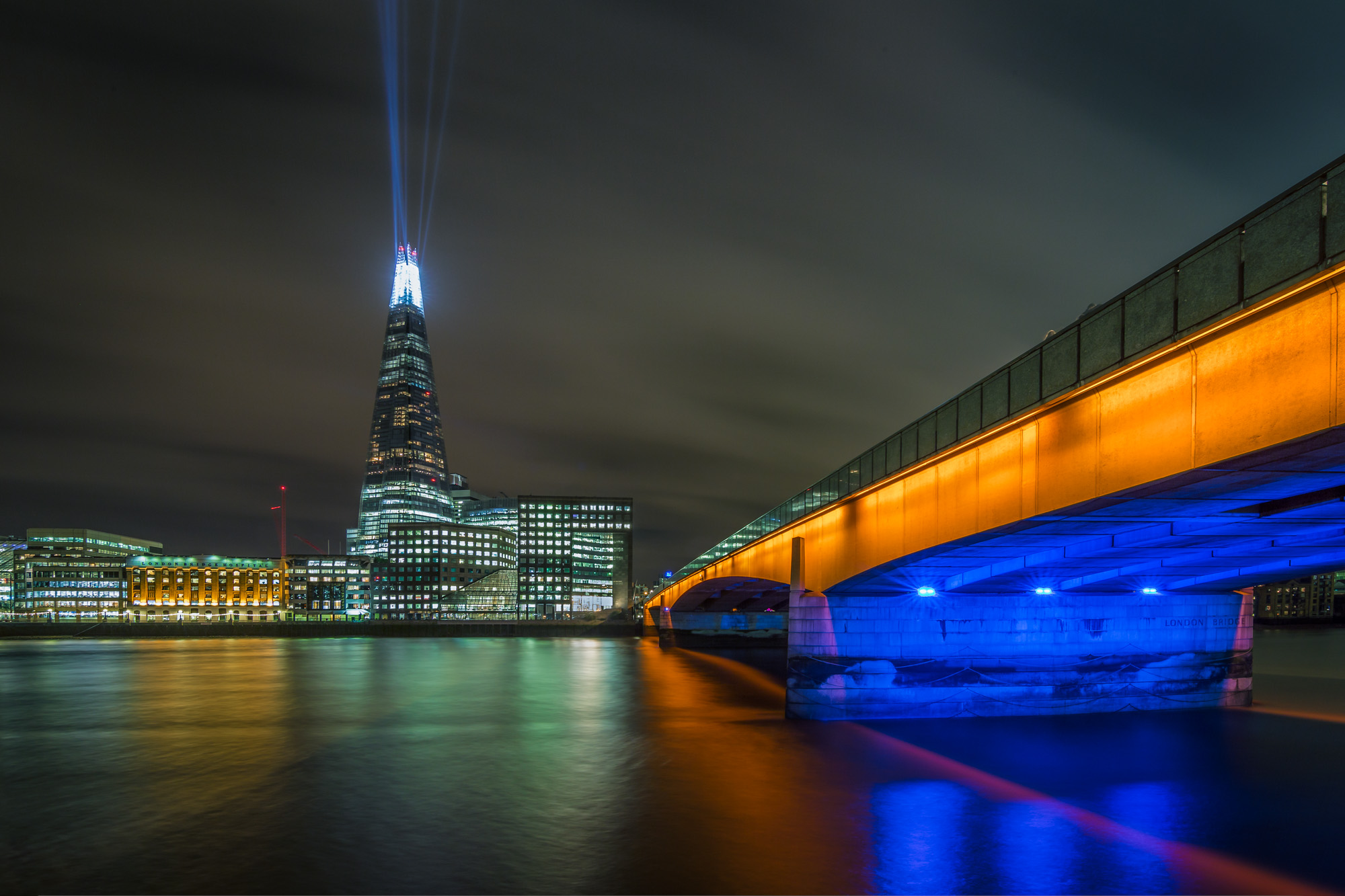 long exposure night photography of a laser light show from the Shard building by the river Thames and London Bridge i