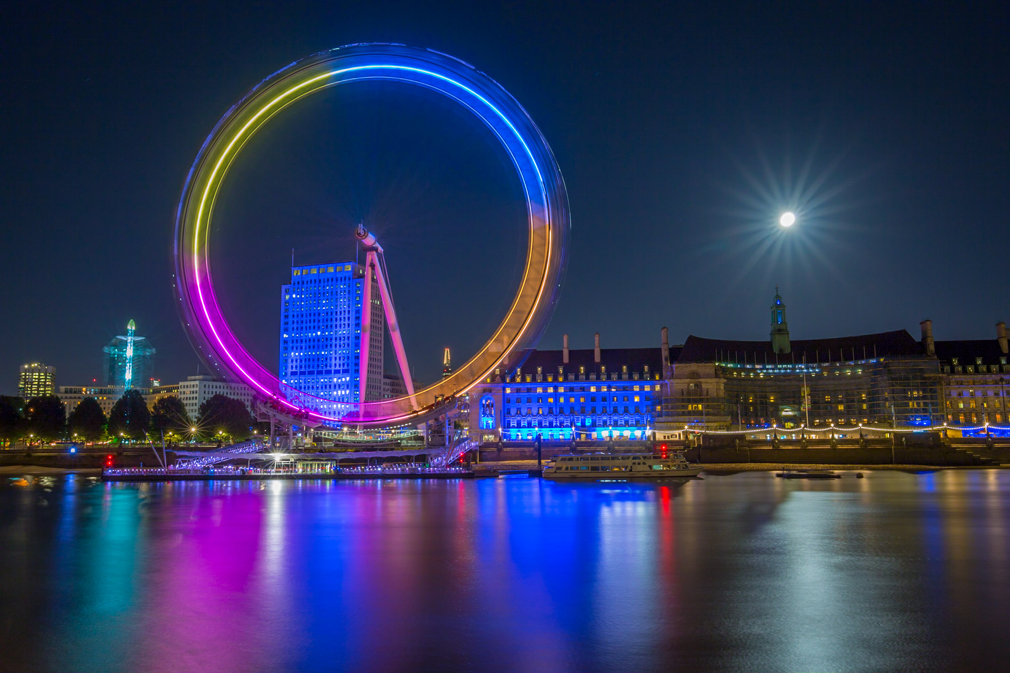 long exposure night photography of a full moon next to the illuminated and rotating London Eye Tourist attraction in London UK