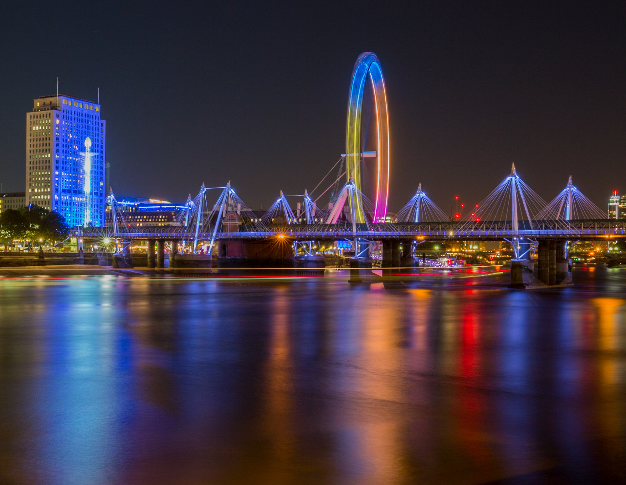 long exposure night photography of viewed down the River Thames of the London Eye and Hungerford Bridge in lights