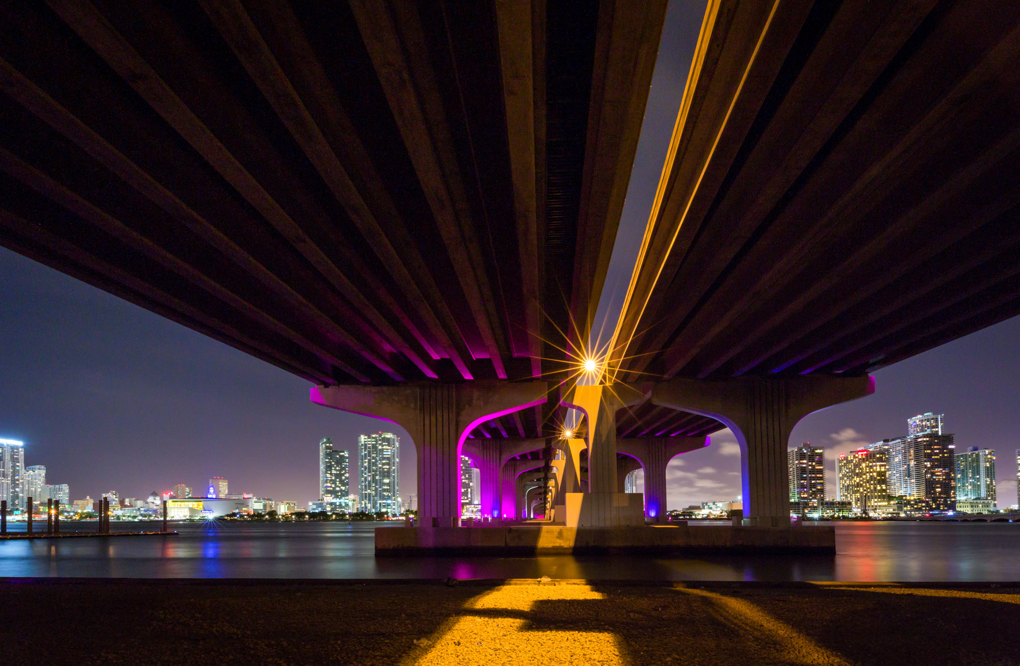 long exposure night photography of Miami skyline from underneath the Rickenbacker Causeway flyover in Florida USA
