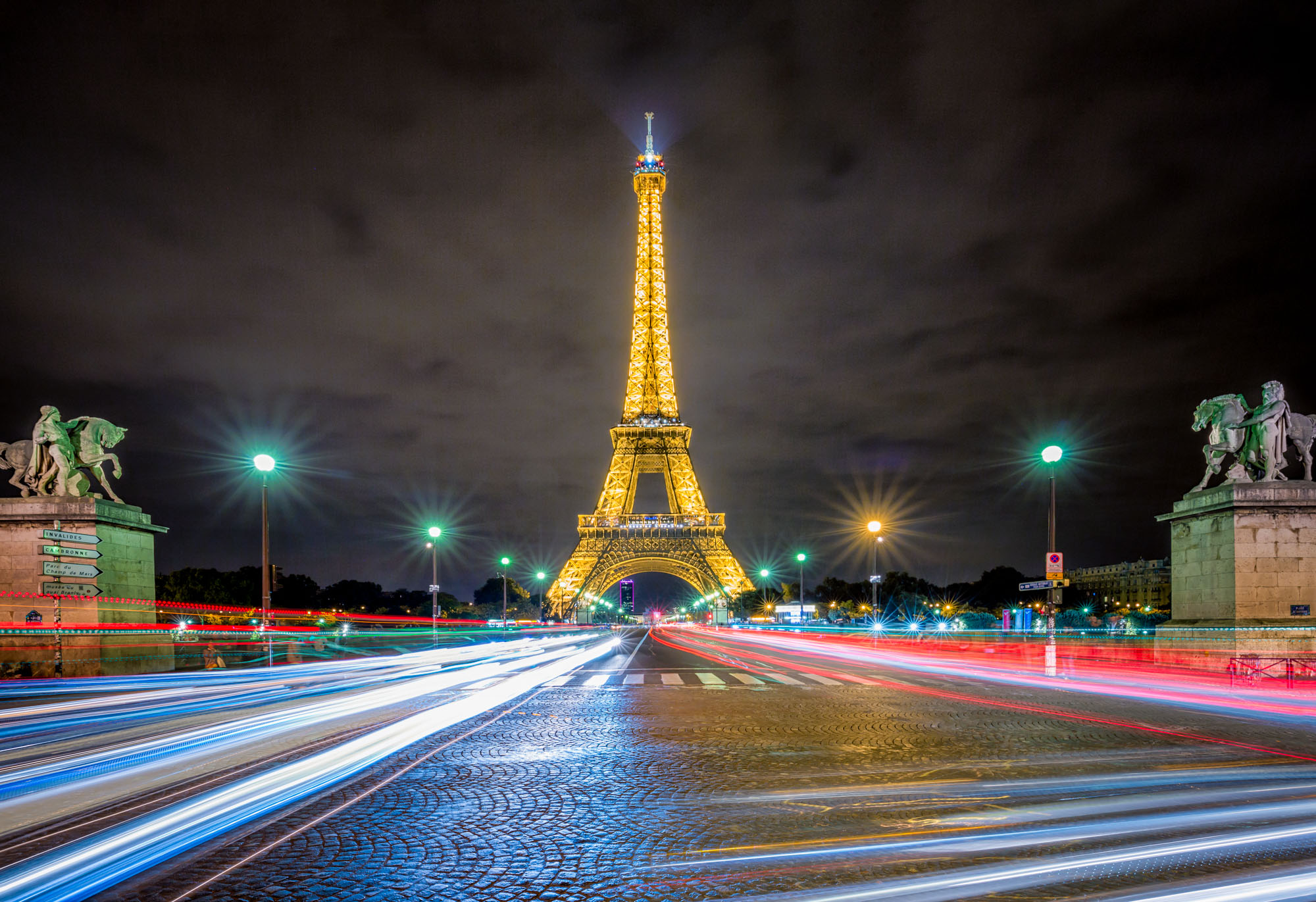long exposure night photography of the Eiffel Tower in Paris France viewed from the roadside capturing traffic as light trails