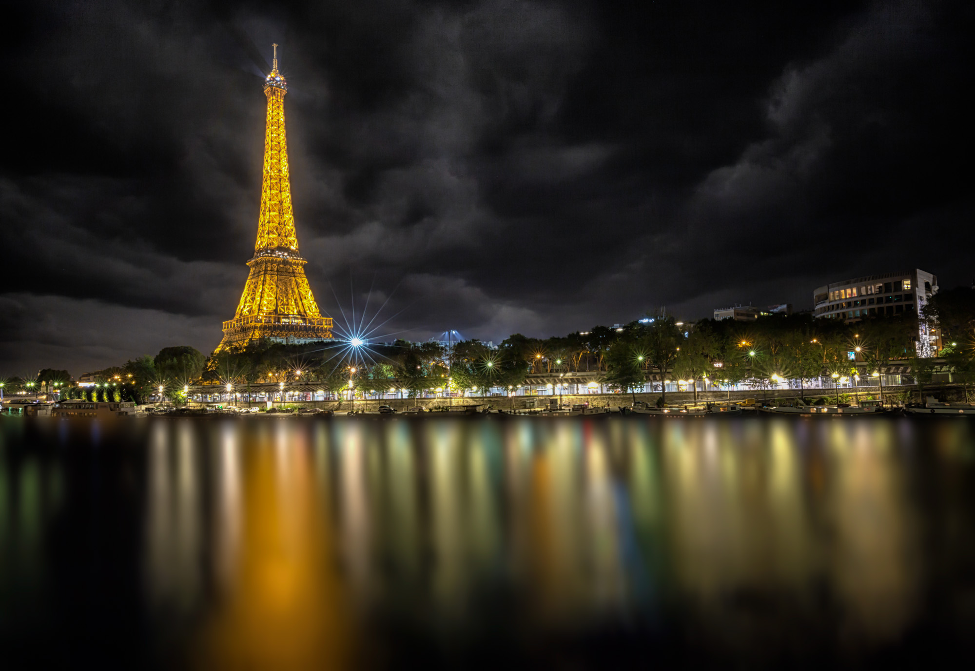 long exposure night photography of the Eiffel Tower and Paris lights at night viewed from the River Seine