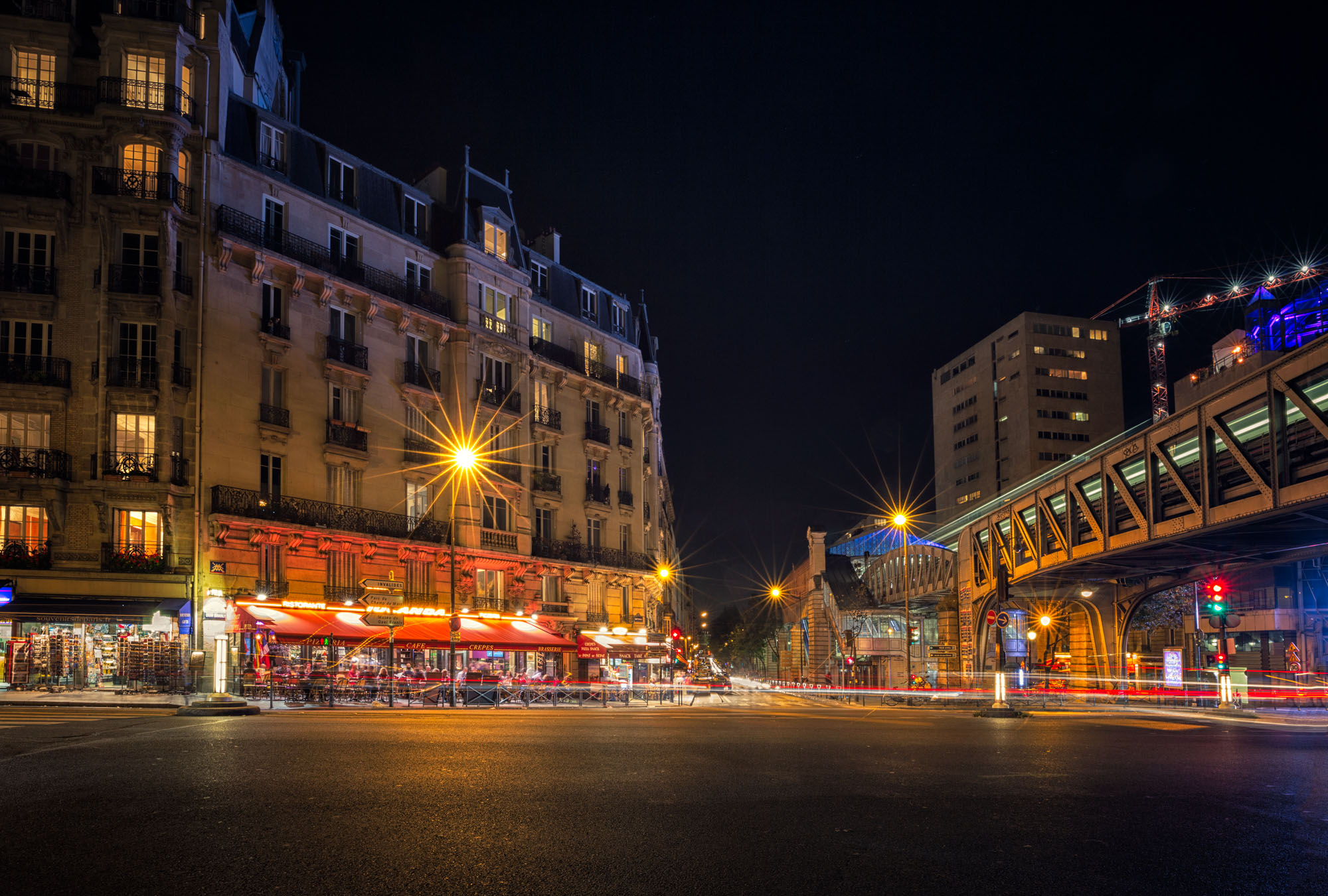 long exposure photography of a cafe in Paris with lights trails and the Metro train