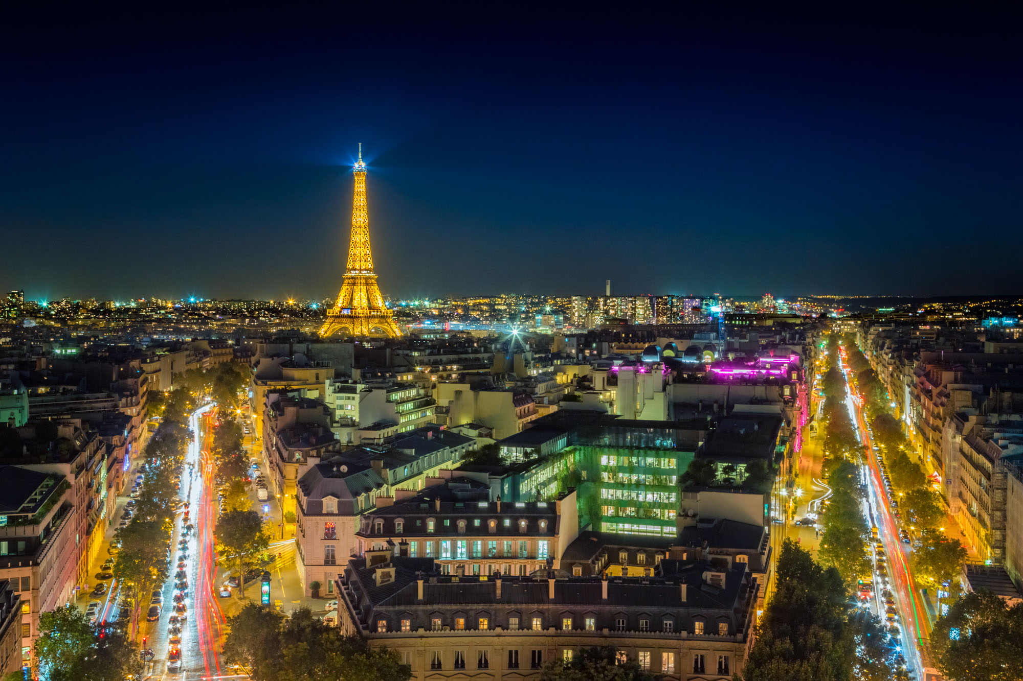 long exposure night photography of the Boulevards in Paris and Eiffel Tower with light trails at sunset viewed from above