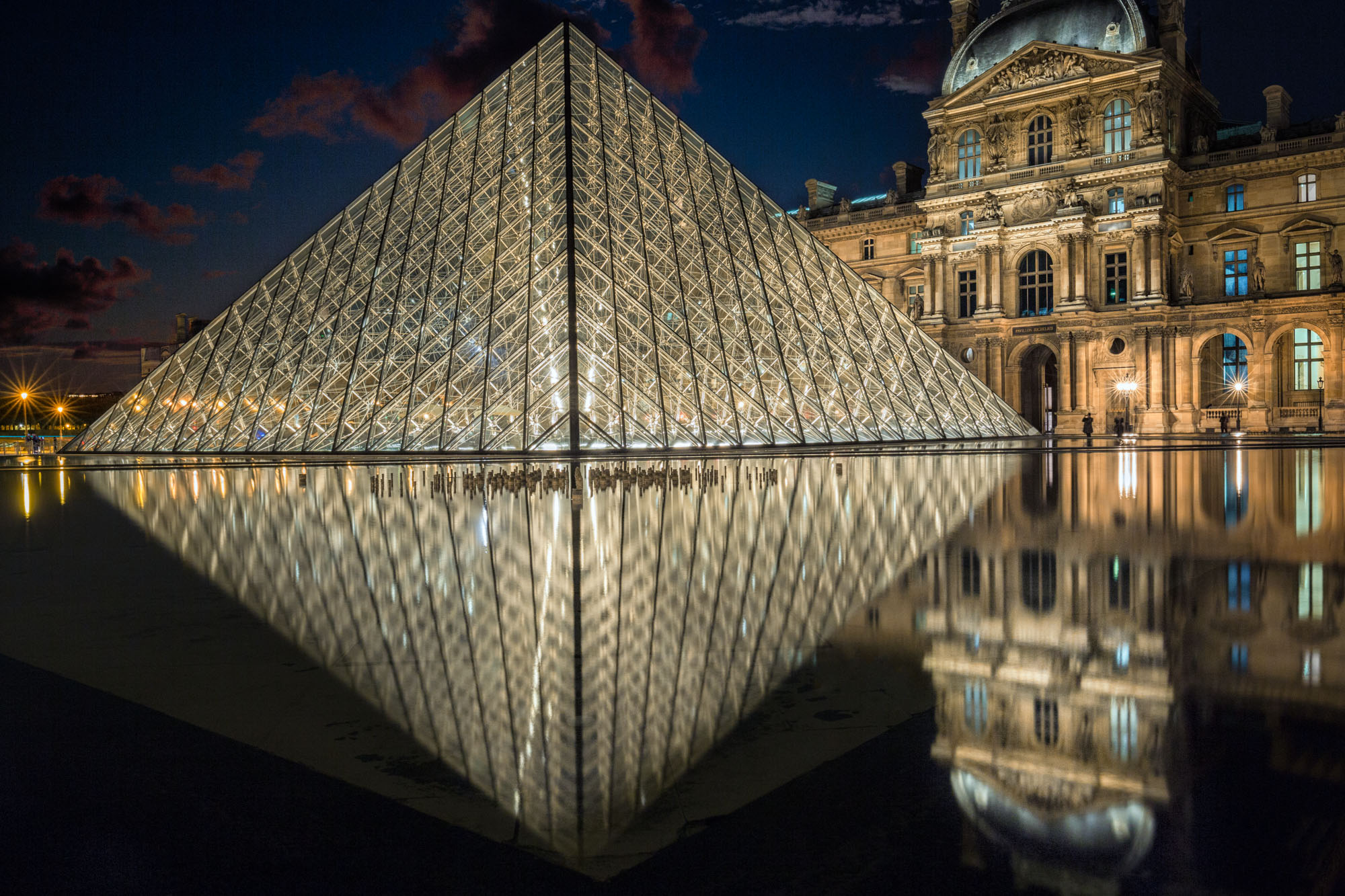 long exposure night photography of the Louvre Museum reflected in water in Paris France